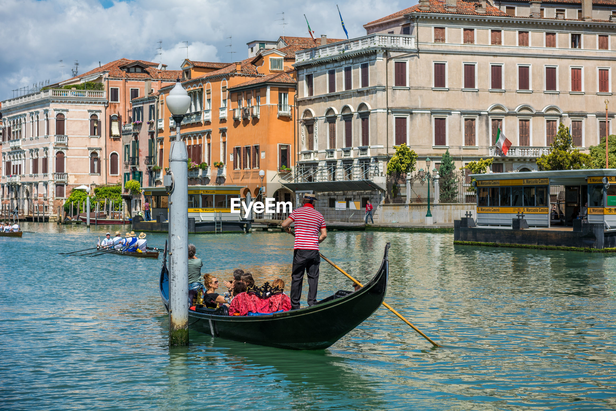 building exterior, architecture, transportation, gondola - traditional boat, built structure, real people, nautical vessel, canal, mode of transport, gondola, gondolier, men, tourism, travel destinations, day, water, women, outdoors, leisure activity, moored, vacations, large group of people, oar, rowing, city, nature, sky, young adult, adult, people