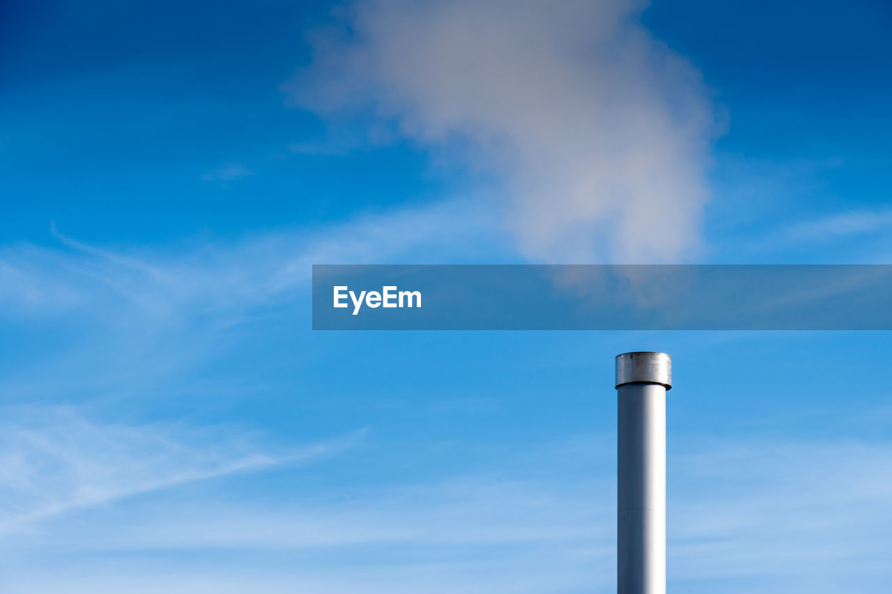 sky, cloud - sky, factory, pollution, smoke stack, blue, emitting, industry, low angle view, smoke - physical structure, environmental issues, no people, air pollution, nature, day, environment, building exterior, chimney, built structure, environmental damage, outdoors, fumes