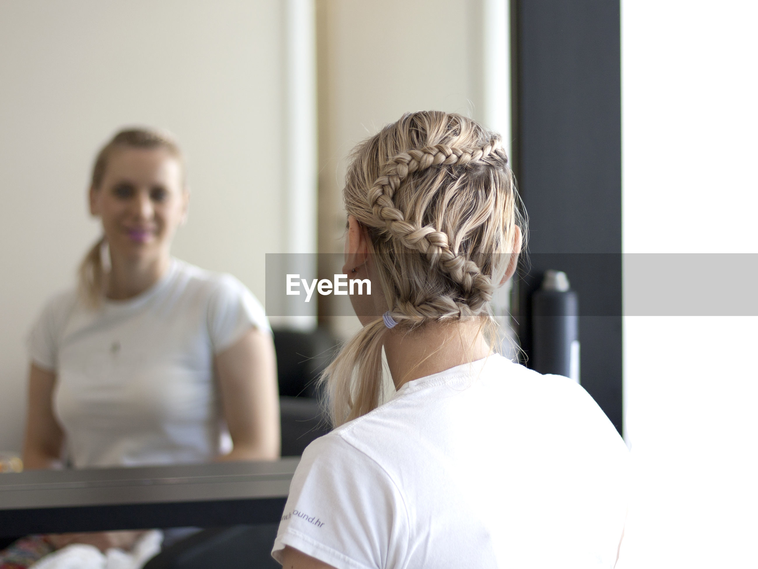 Rear view of woman reflecting in mirror at home