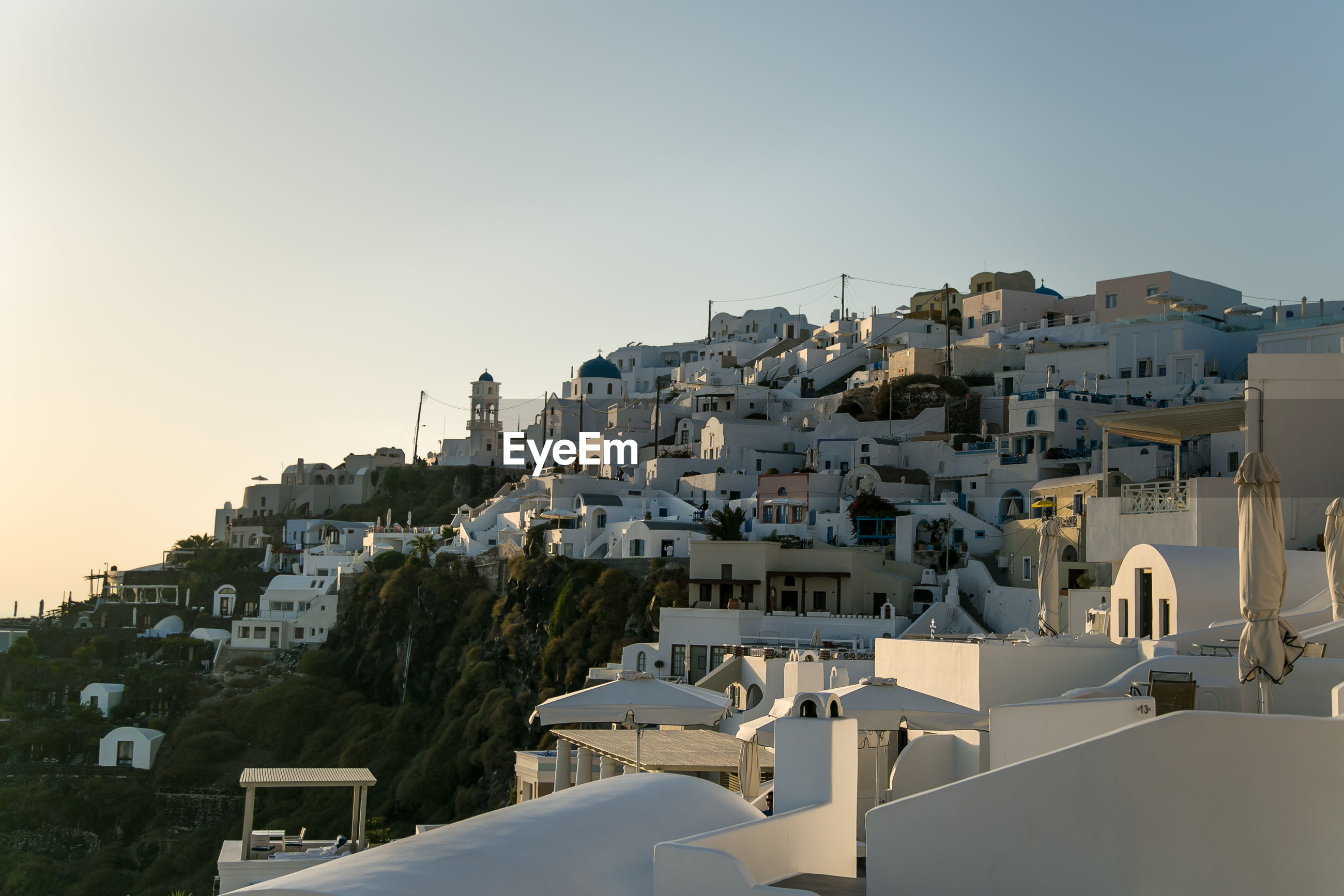 Low angle view of buildings on mountain against clear sky during sunset