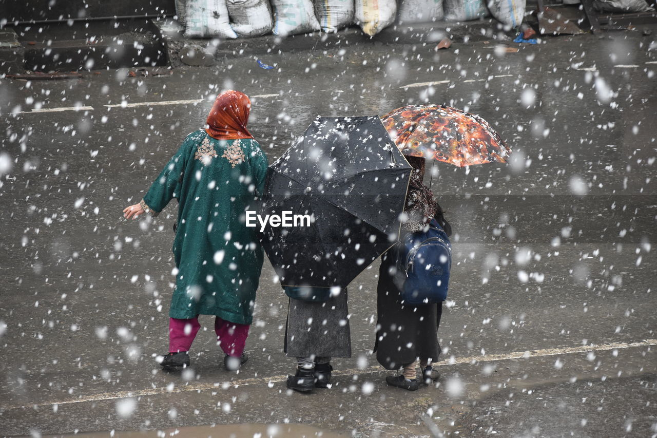winter, snow, cold temperature, snowing, two people, warm clothing, full length, clothing, child, nature, females, togetherness, men, males, people, storm, snowflake, family, childhood, blizzard, outdoors, extreme weather