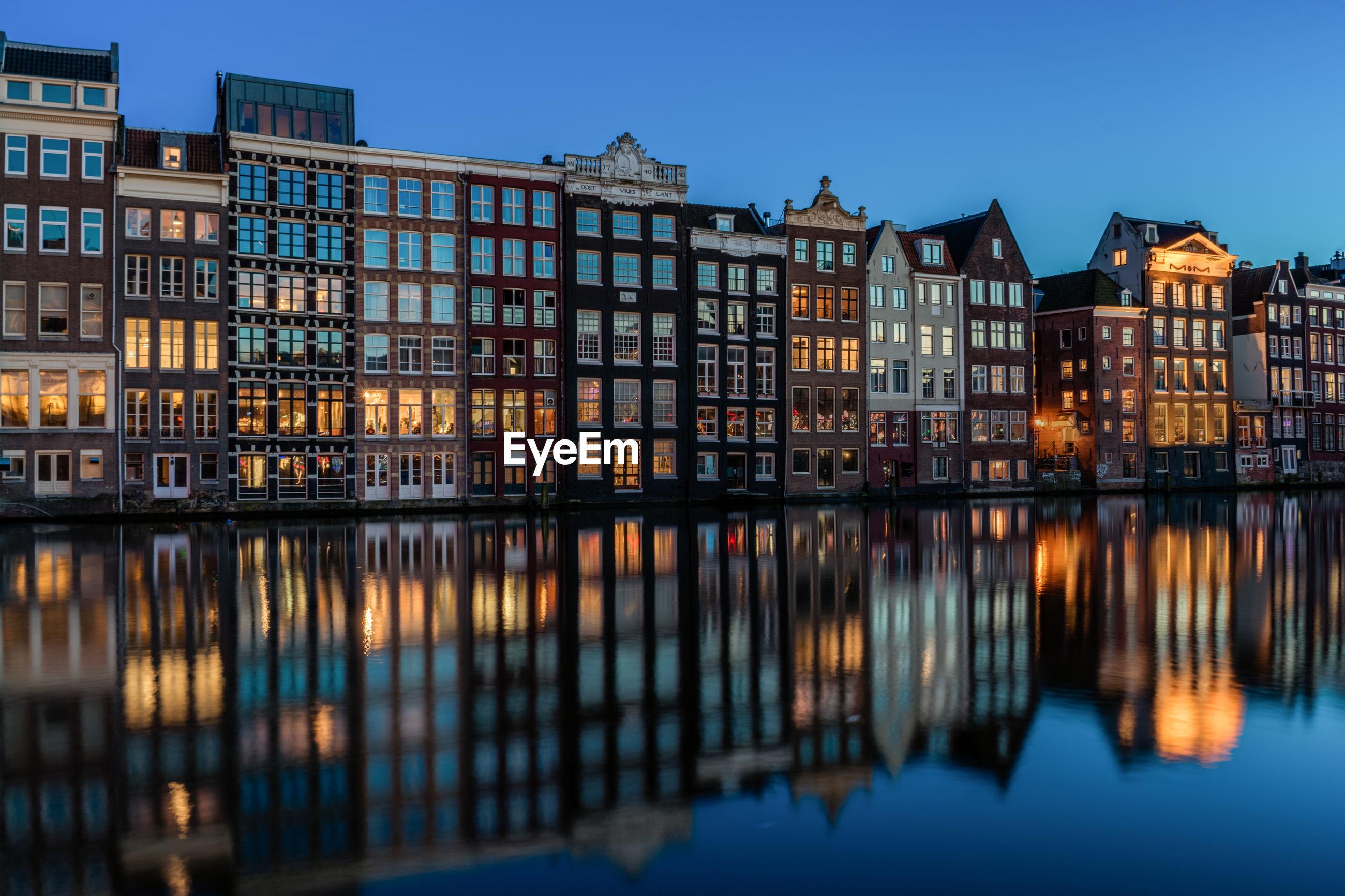 Reflection of illuminated row houses on canal at dusk