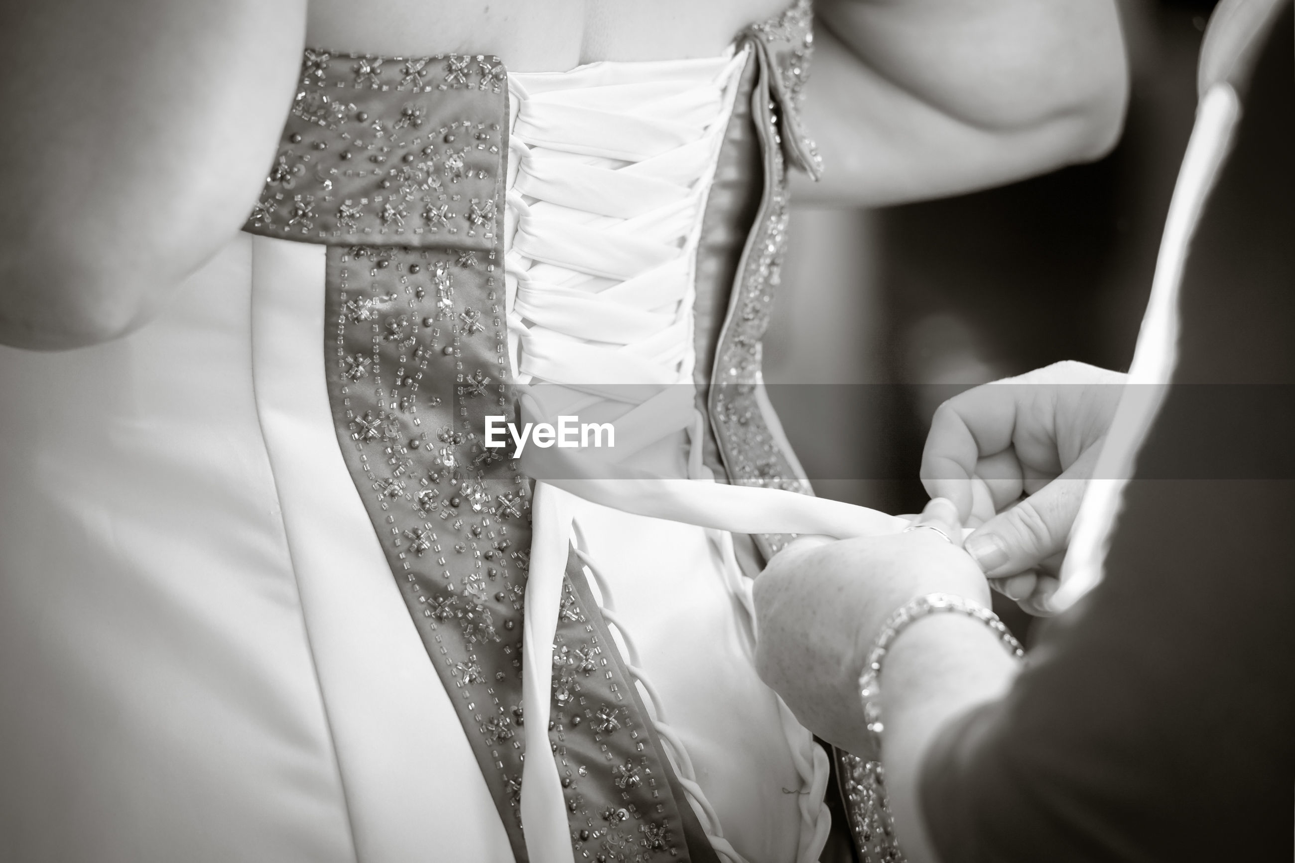 Cropped hands of woman assisting bride in dressing up