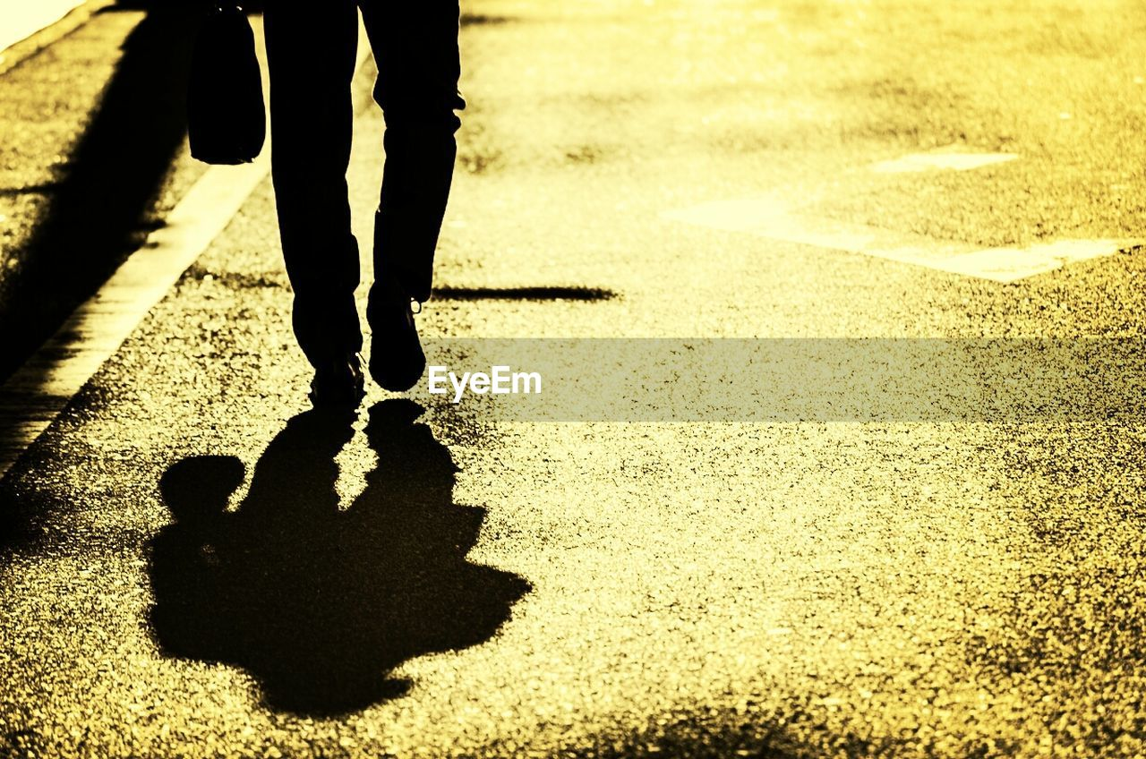 Low section of a man with shadow walking on street