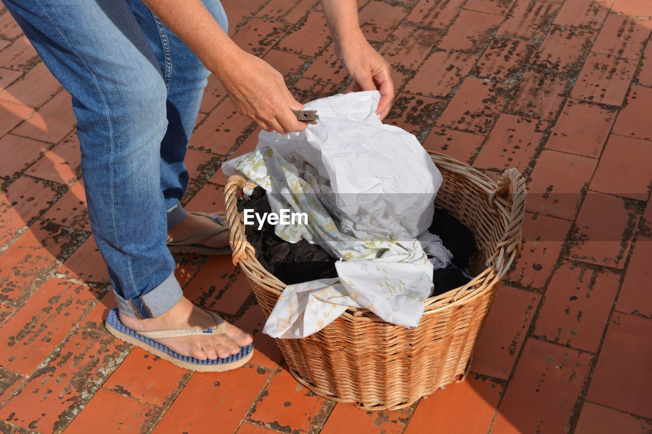 Low Section Of Woman Picking Up Cloth From Basket