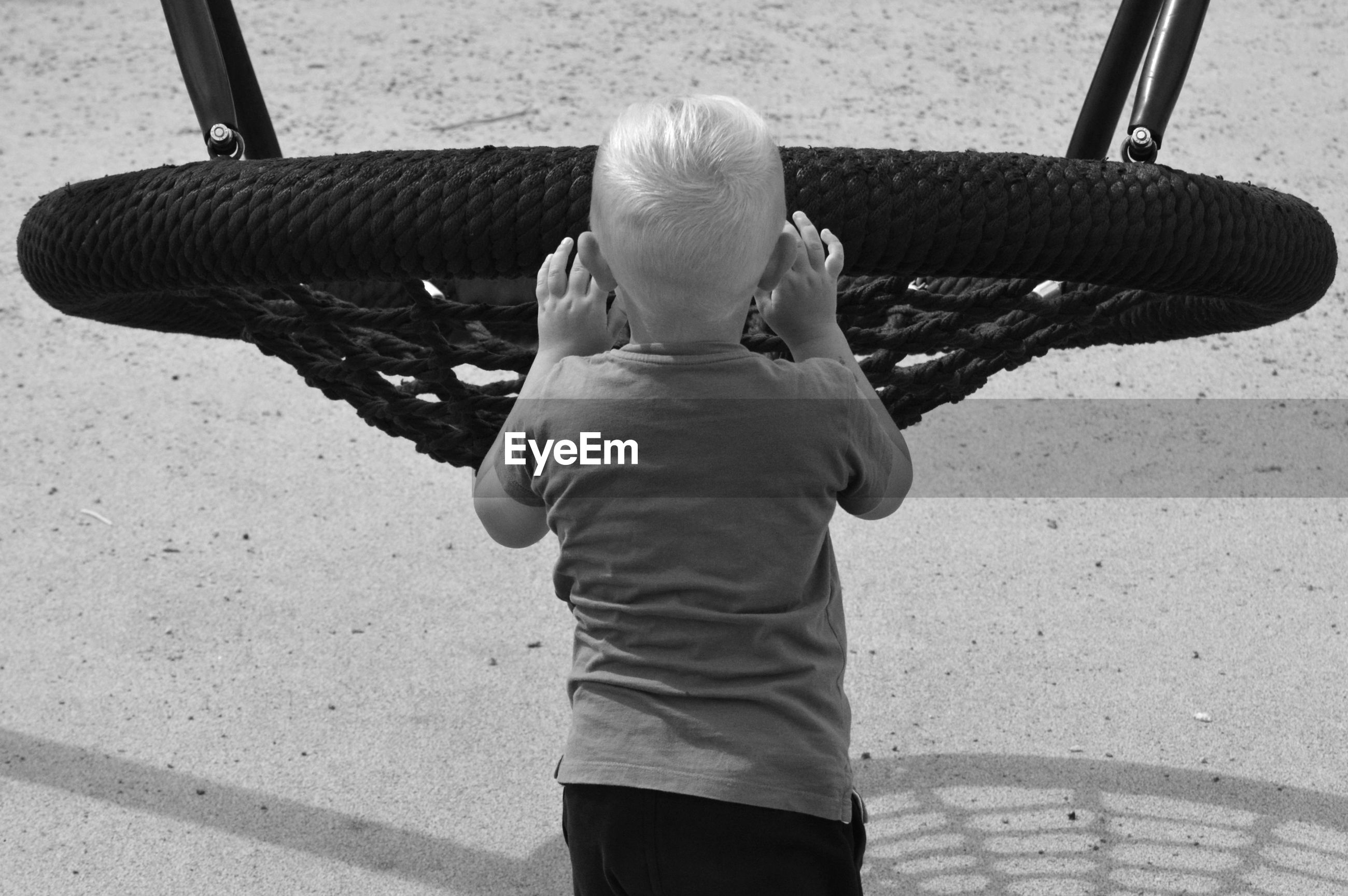 Rear view of boy standing by swing in playground