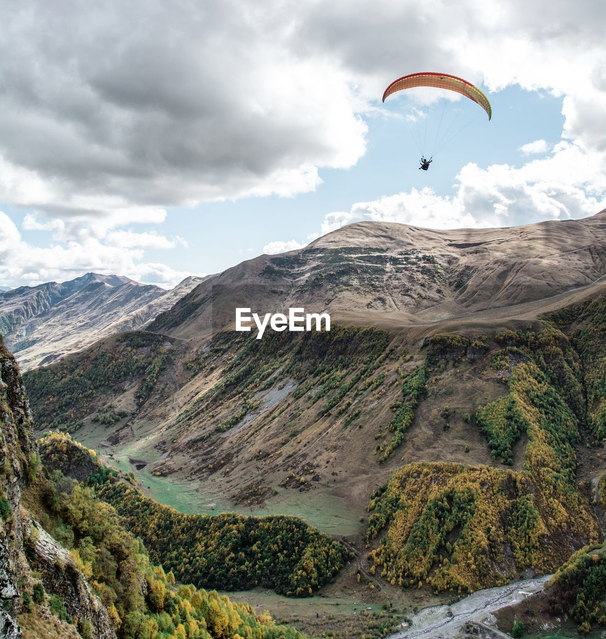 Man Paragliding Over Mountain Against Cloudy Sky