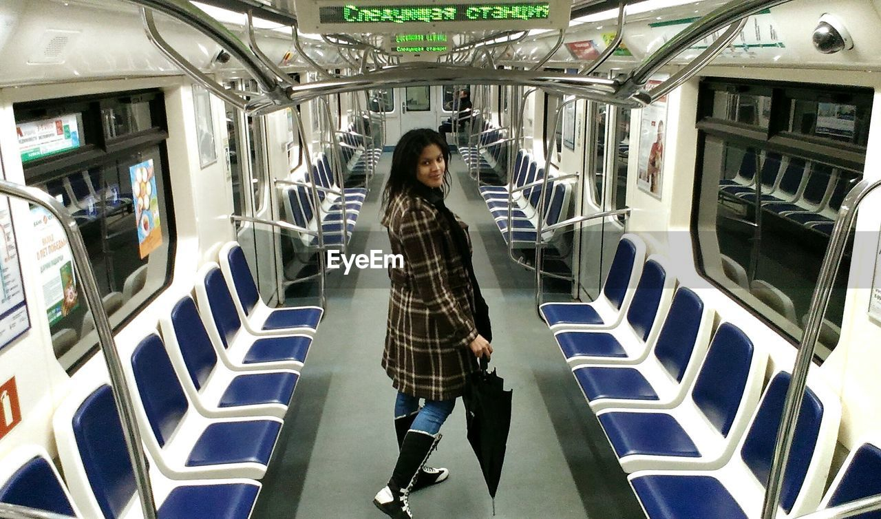 public transportation, one person, full length, real people, casual clothing, train - vehicle, transportation, standing, lifestyles, looking at camera, subway train, young adult, portrait, vehicle seat, commuter, journey, young women, commuter train, indoors, day, adults only, adult, people