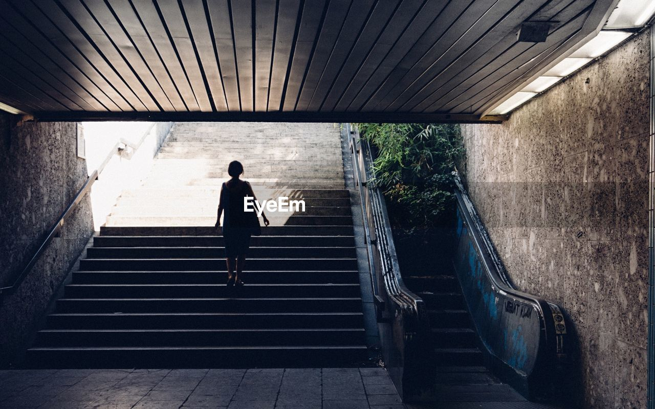 Rear view of woman on steps in tunnel