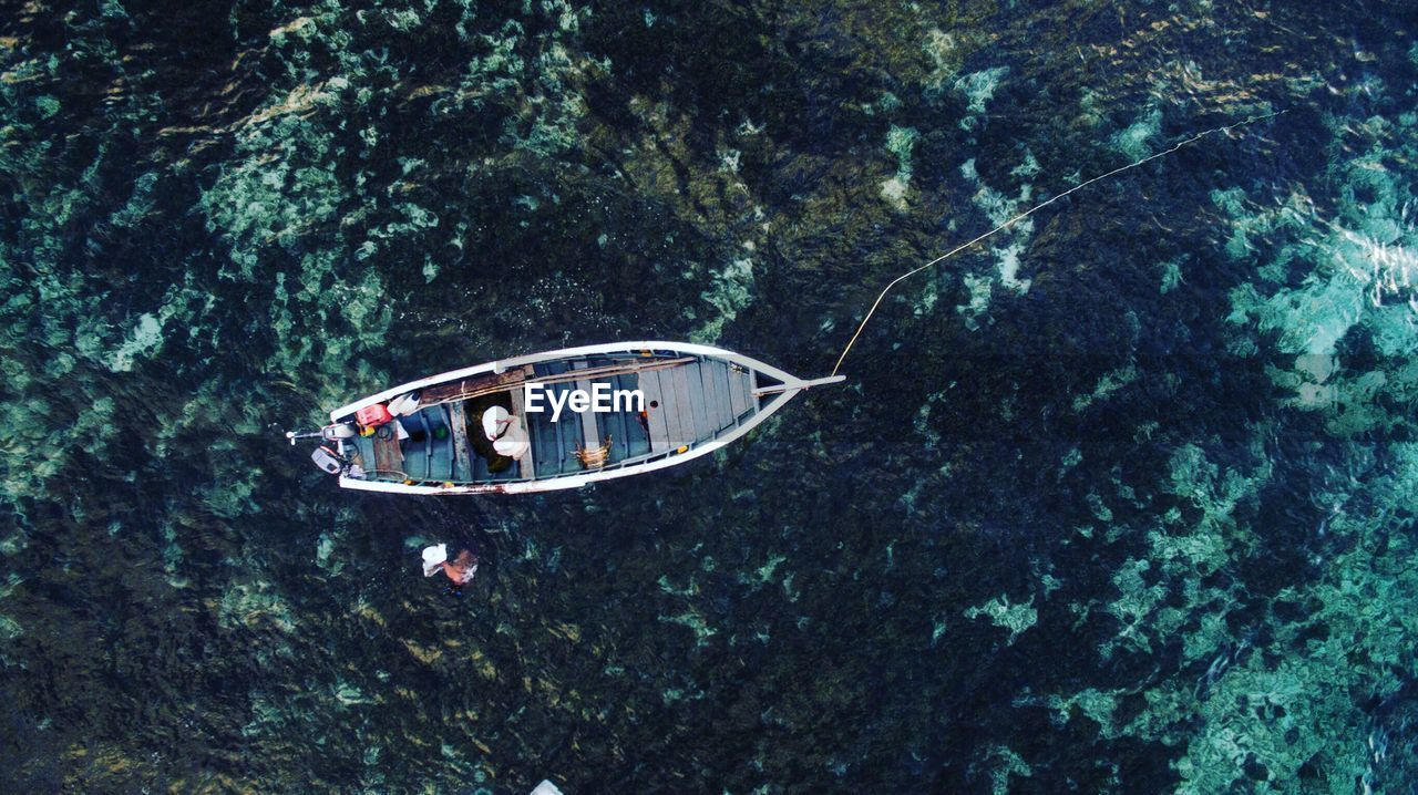 High angle view of fisherman sitting in boat