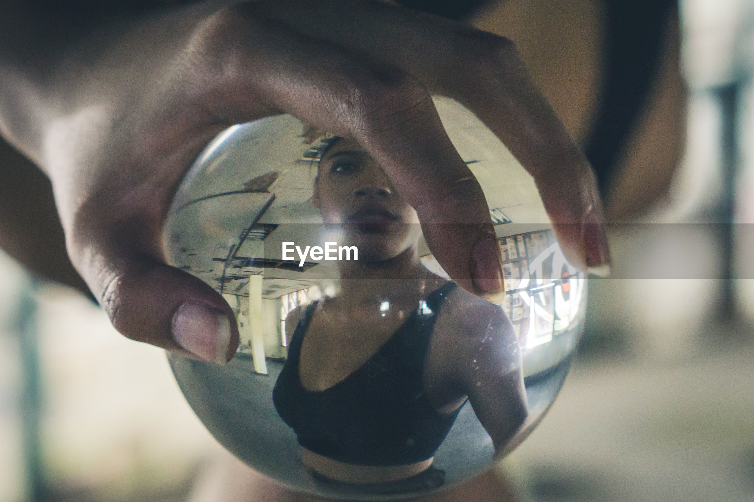Cropped hand touching crystal ball with reflection of woman
