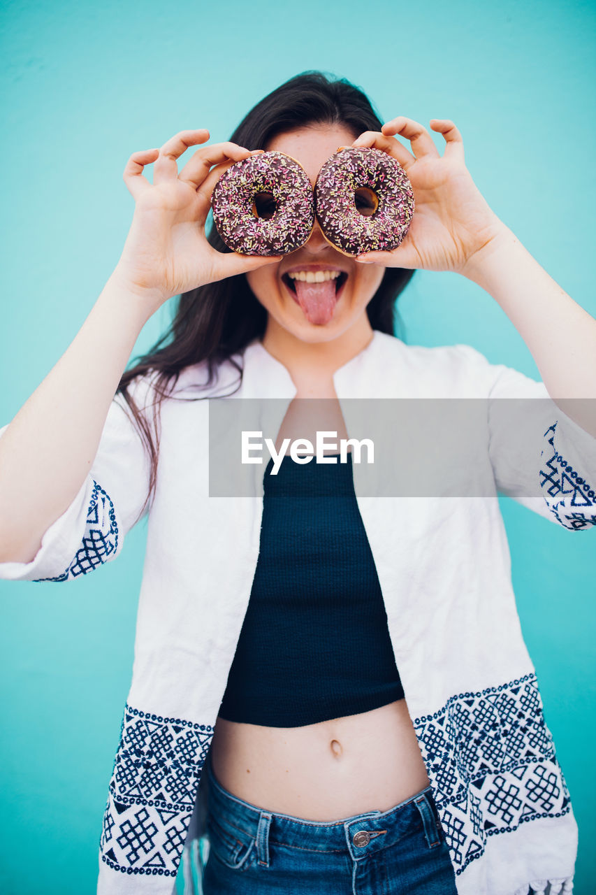 Portrait Of Young Woman Holding Donuts While Standing Against Blue Background