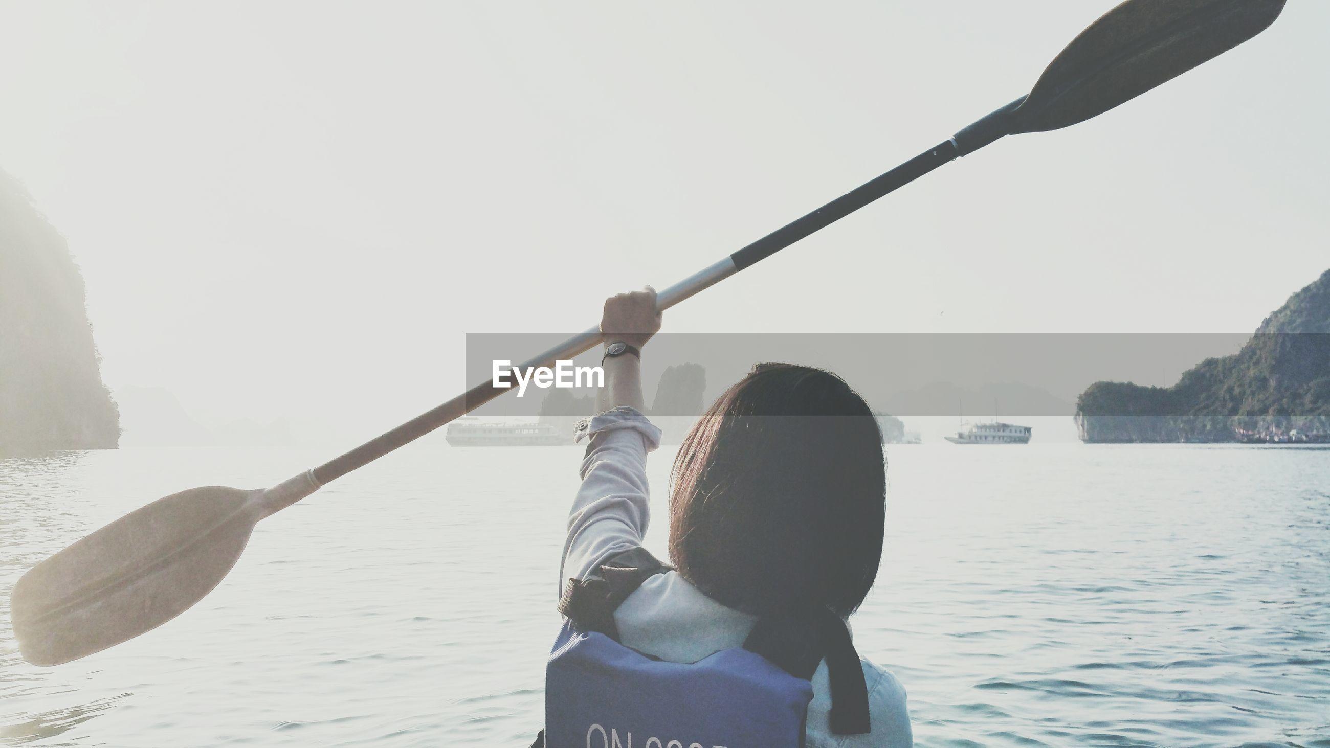 Rear view of woman holding oar on lake