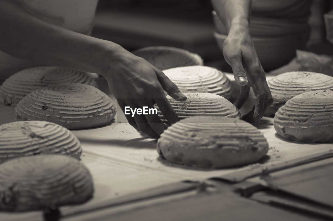 Cropped Image Of Baker Making Bread At Bakery