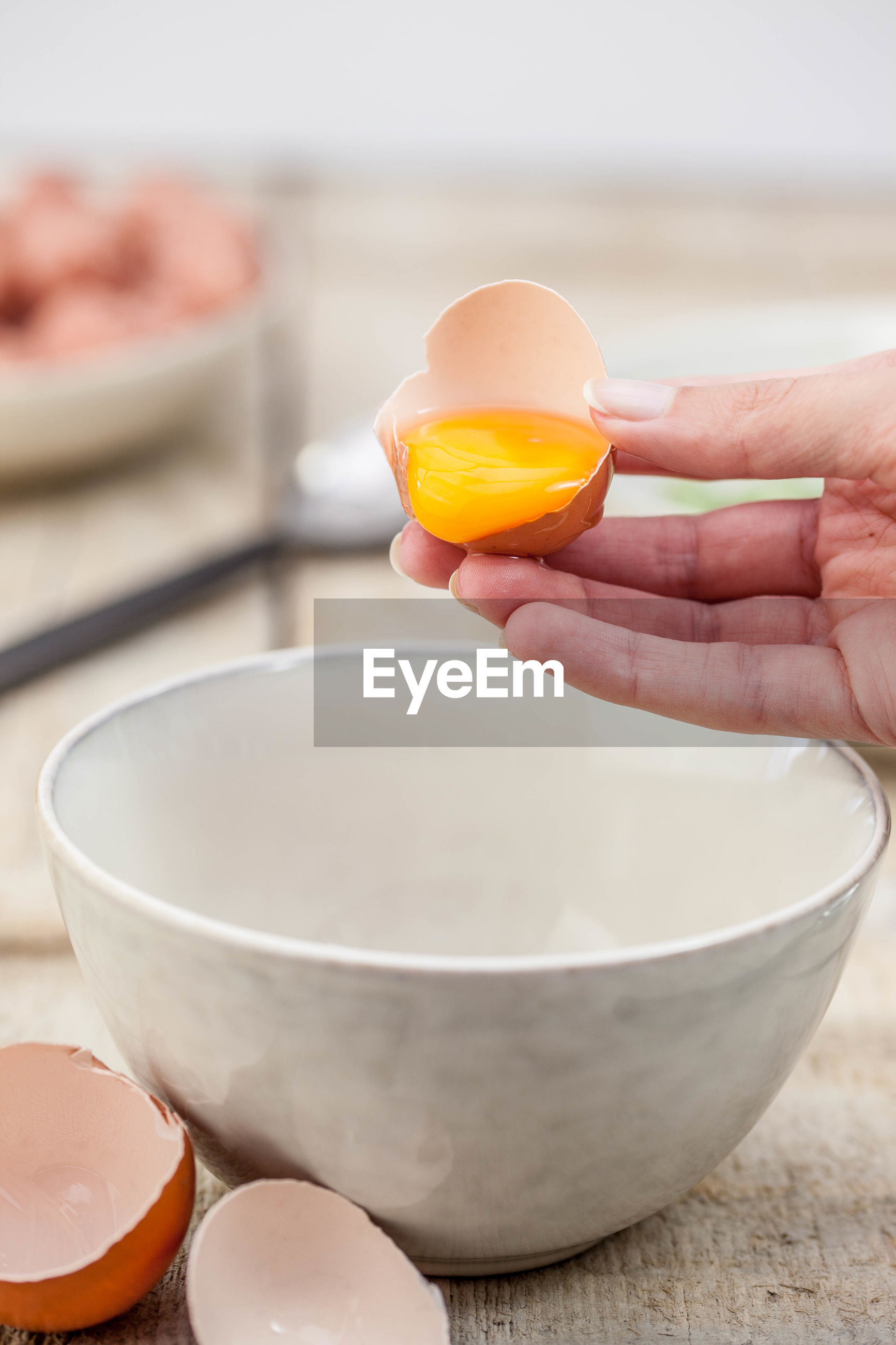 Cropped image of hand pouring egg in bowl