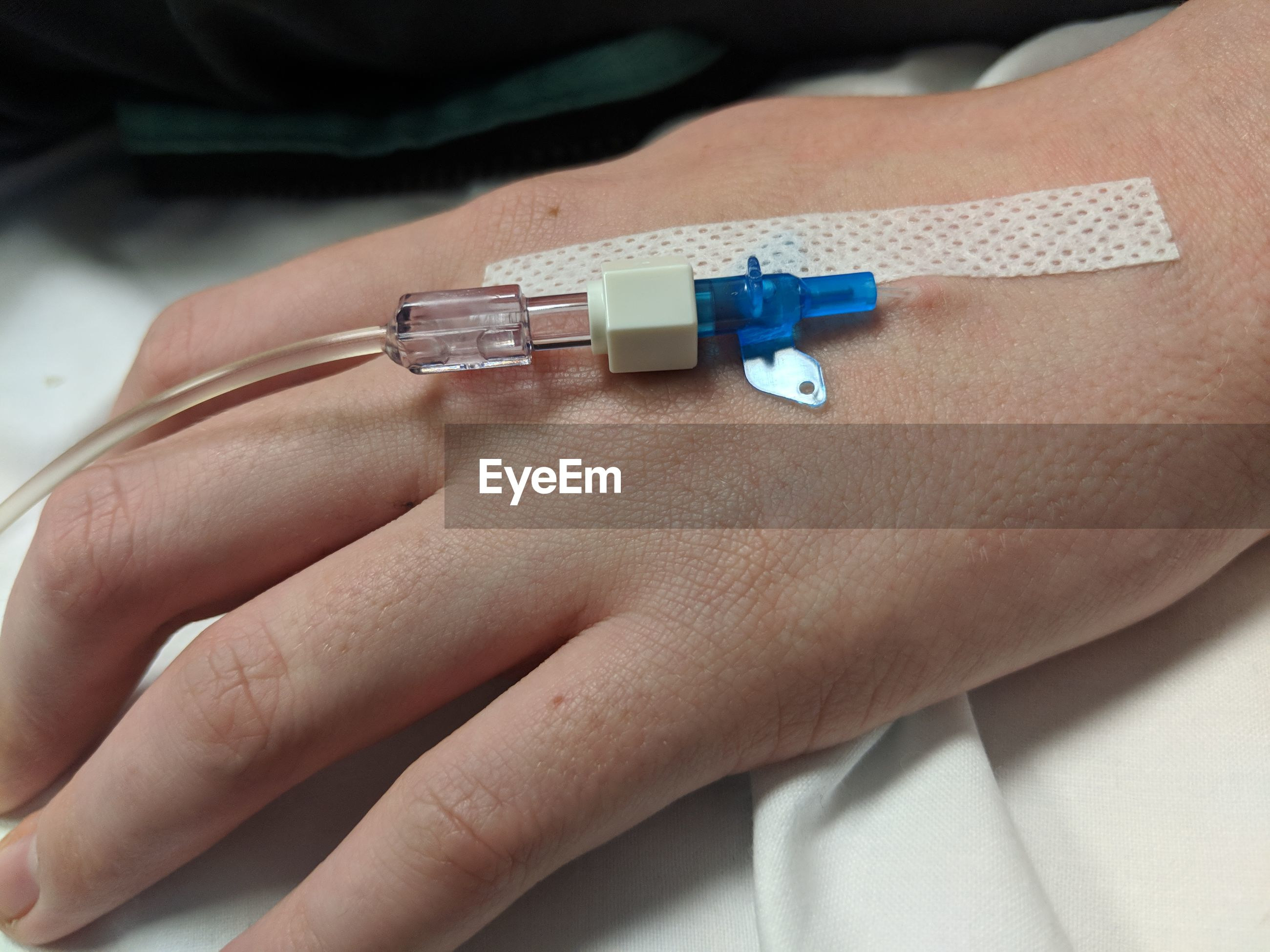 Cropped hand of patient wearing iv drip in hospital