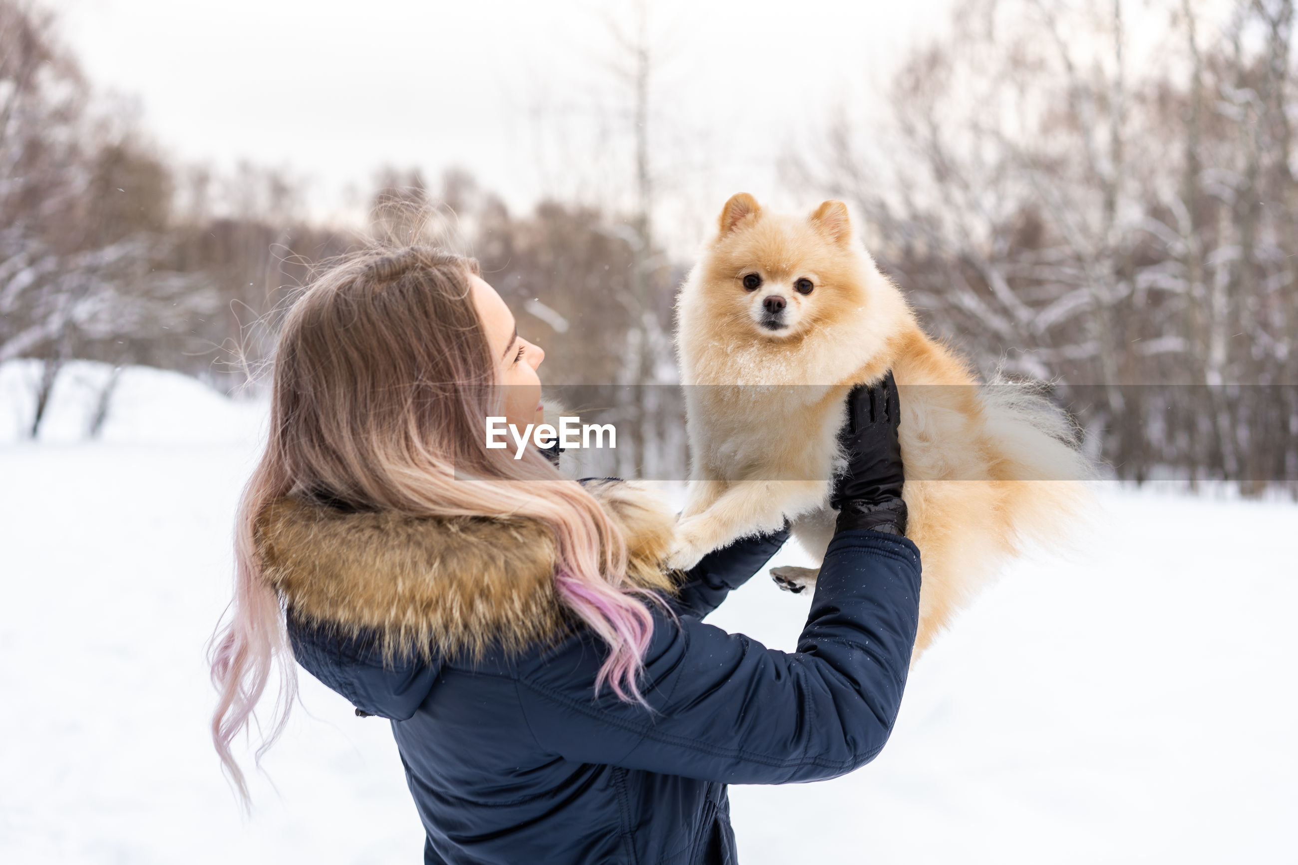 Young woman carrying dog while standing in snow during winter