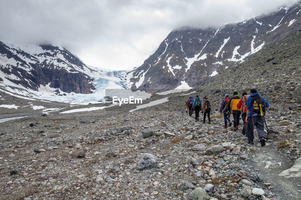 Rear view of people hiking on rocky landscape against snowcapped mountains