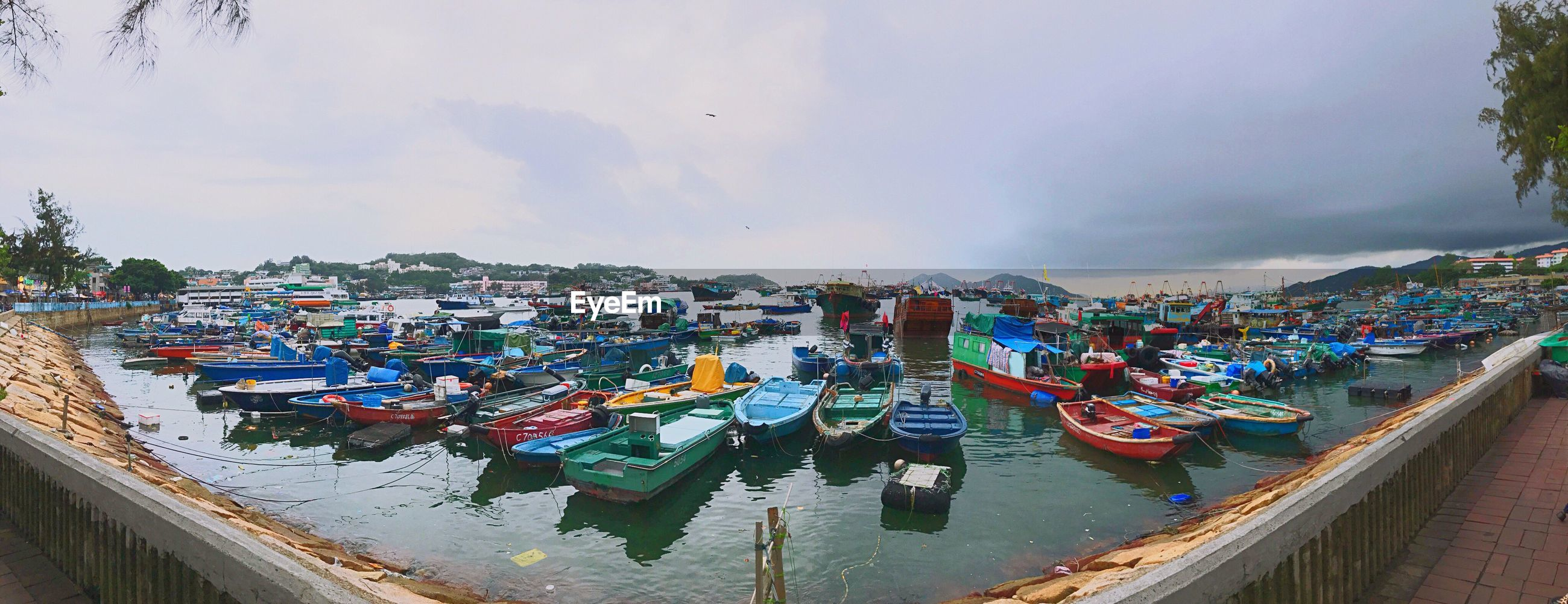 Panoramic image of boats moored at harbor in city
