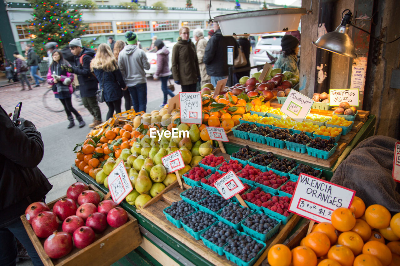 fruit, market, market stall, food, food and drink, freshness, variation, healthy eating, outdoors, choice, retail, day, for sale, peach, vegetable, price tag, abundance, grape, large group of objects, real people, women, large group of people, men, business, people, city, adult, adults only, supermarket