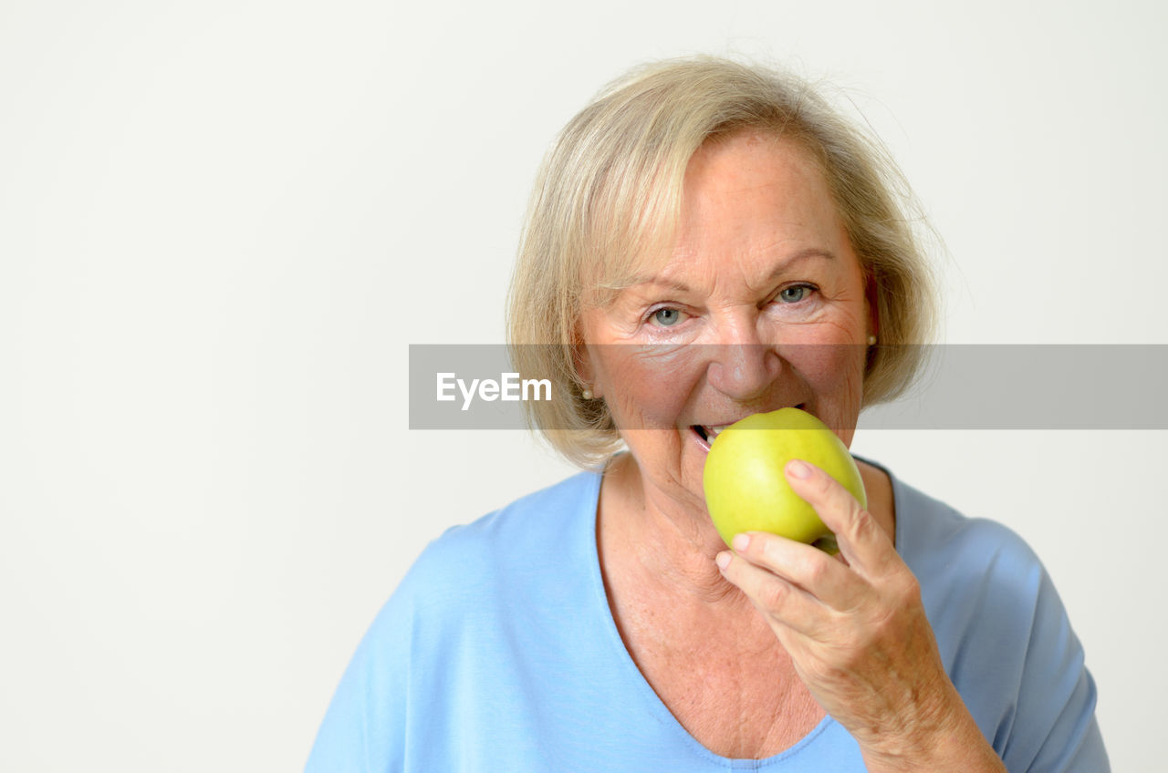 Portrait Of Senior Woman Eating Granny Smith Apple Against Gray Background