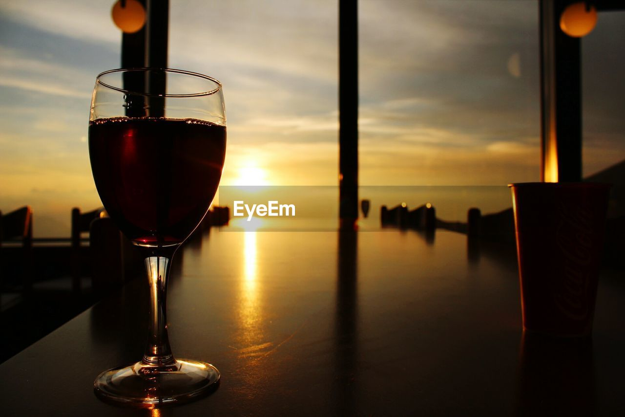 Close-Up Of Wine On Table Against Sky At Sunset