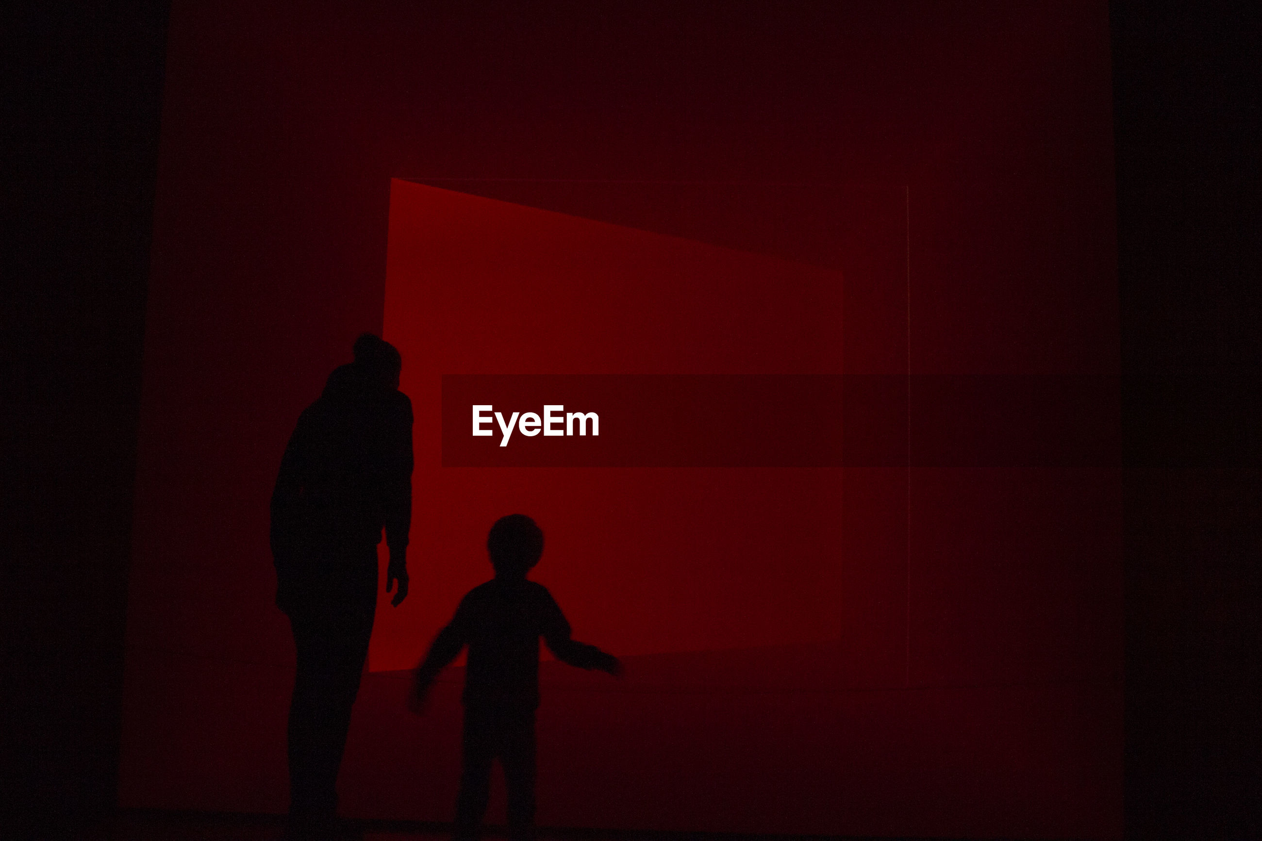 SILHOUETTE OF CHILD STANDING IN RED LIGHT