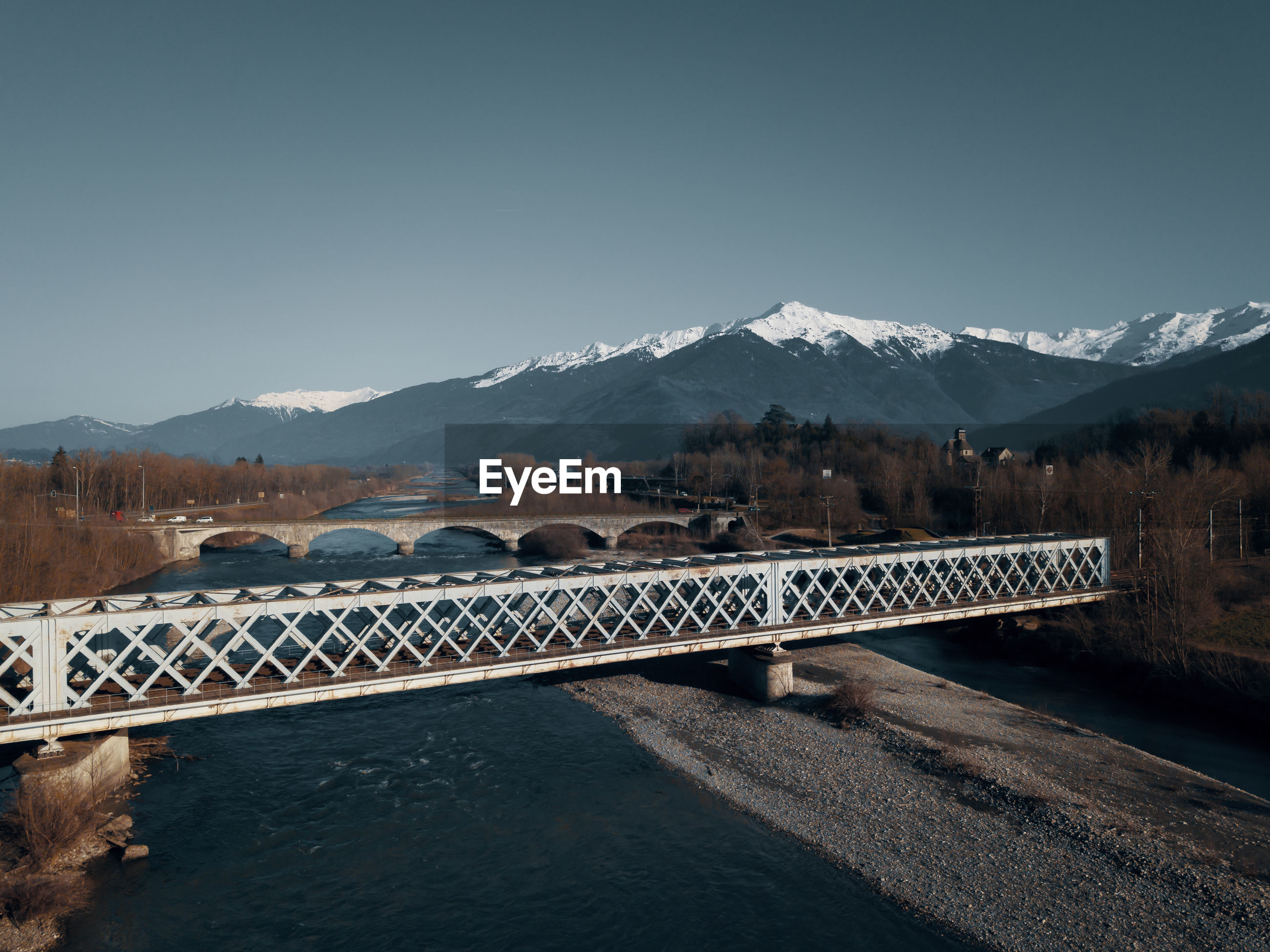 BRIDGE OVER MOUNTAINS AGAINST SKY DURING WINTER