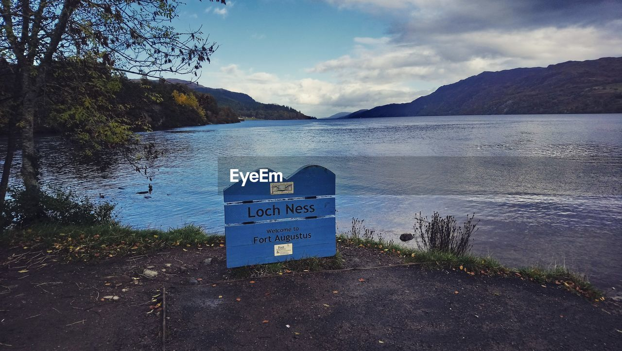 water, sky, text, communication, western script, lake, nature, cloud - sky, mountain, scenics - nature, day, tranquility, beach, beauty in nature, no people, sign, tranquil scene, information, outdoors, message