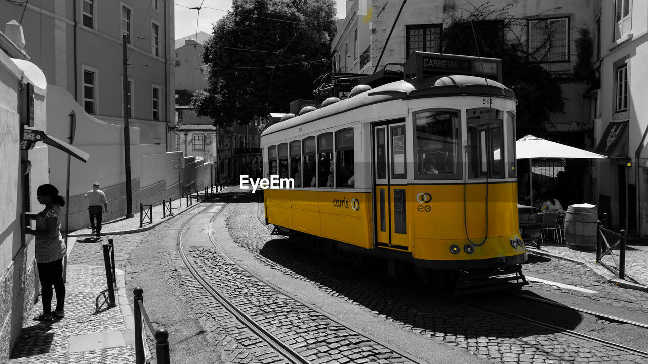 transportation, railroad track, built structure, tramway, mode of transport, public transportation, architecture, street, building exterior, rail transportation, outdoors, day, land vehicle, real people, city, one person, people