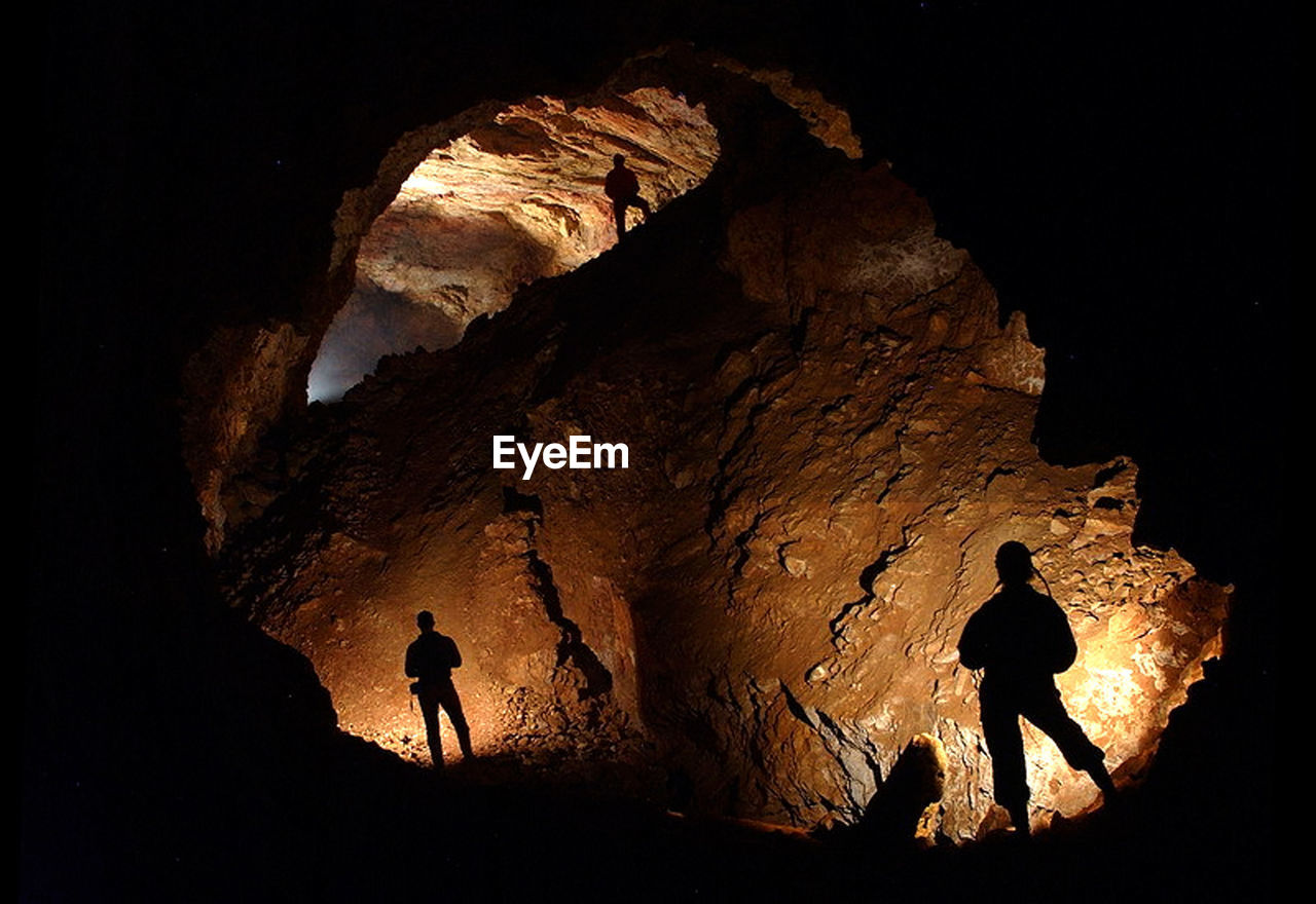 Silhouette People Standing In Cave At Night