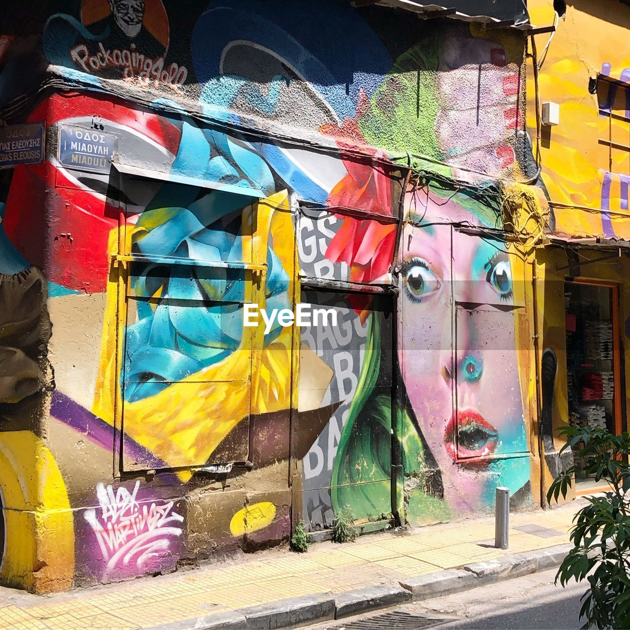 graffiti, multi colored, creativity, day, art and craft, street art, building exterior, architecture, built structure, no people, representation, outdoors, mural, city, yellow, human representation, wall - building feature, nature, sunlight