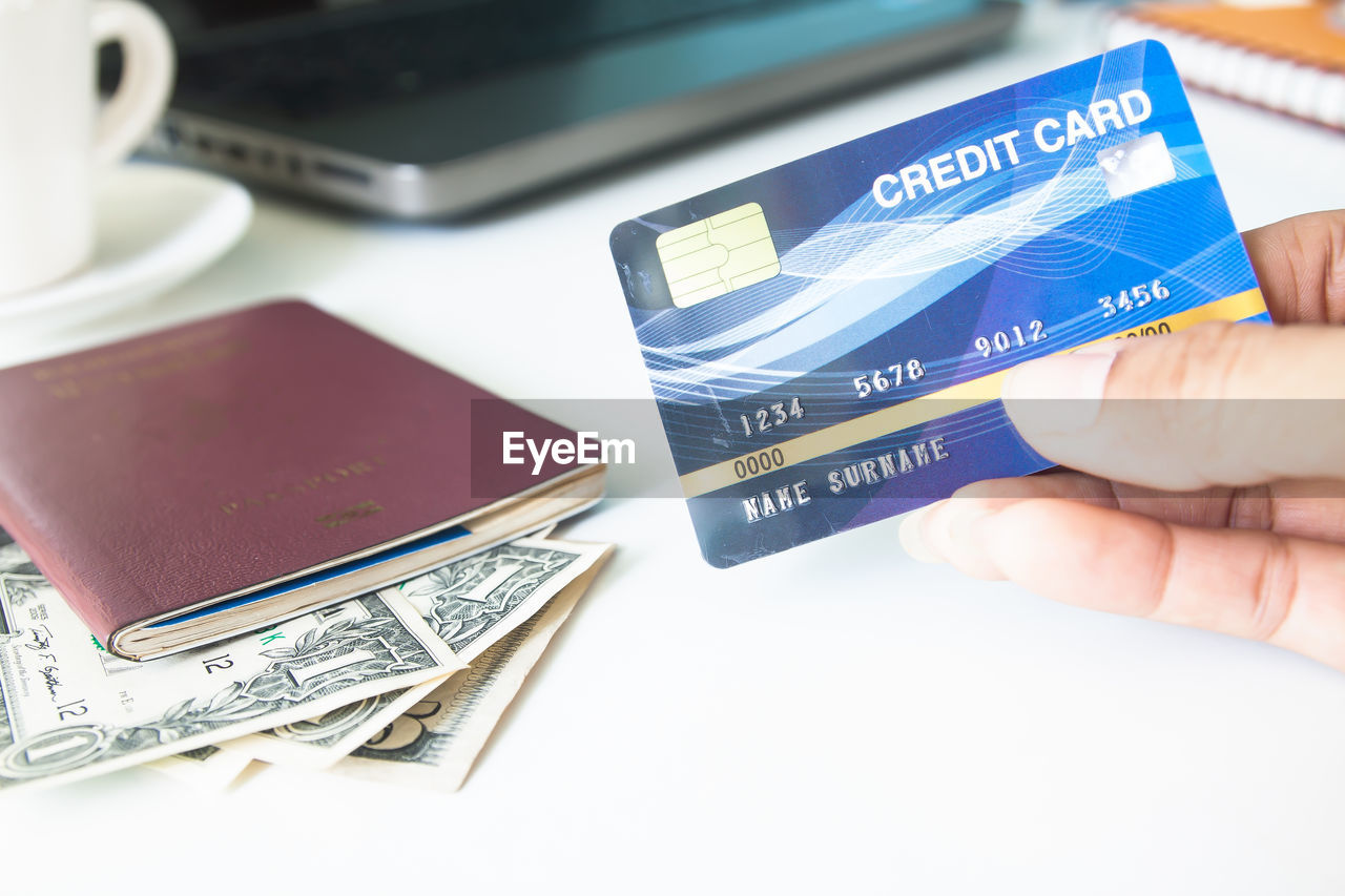 Cropped hand of woman holding credit card on desk in office