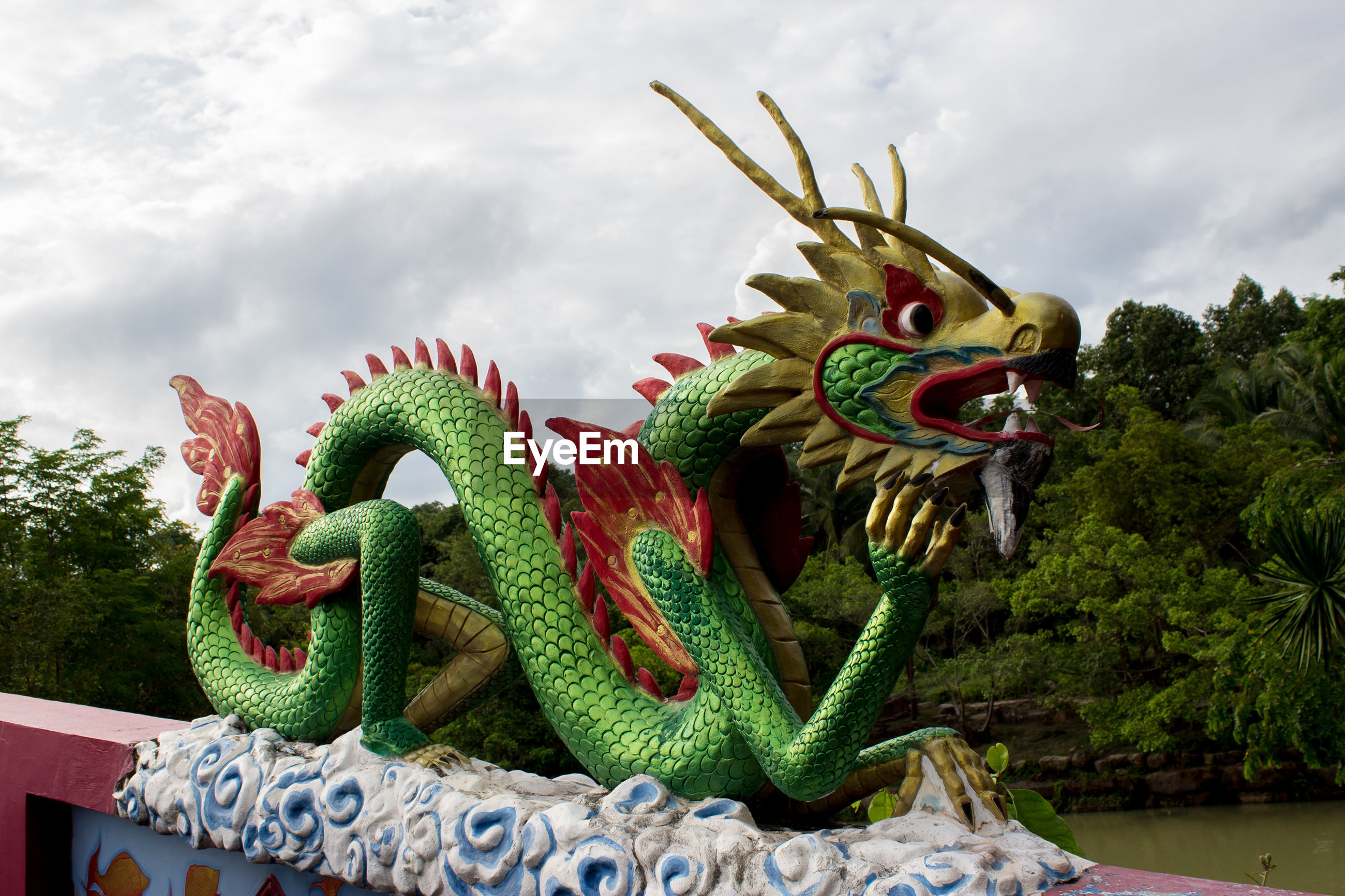 CLOSE-UP OF DRAGON STATUE AGAINST TREES