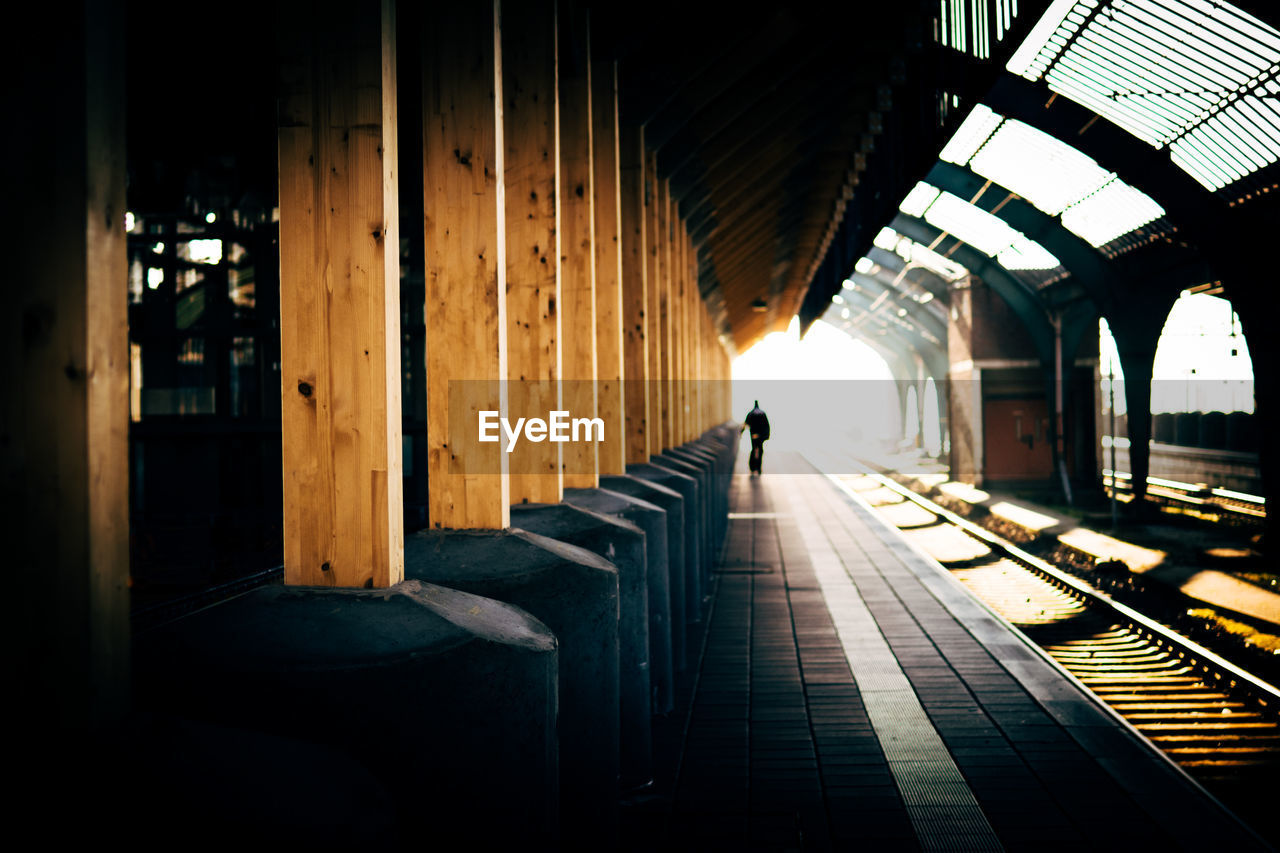Distant view of person on railroad station platform