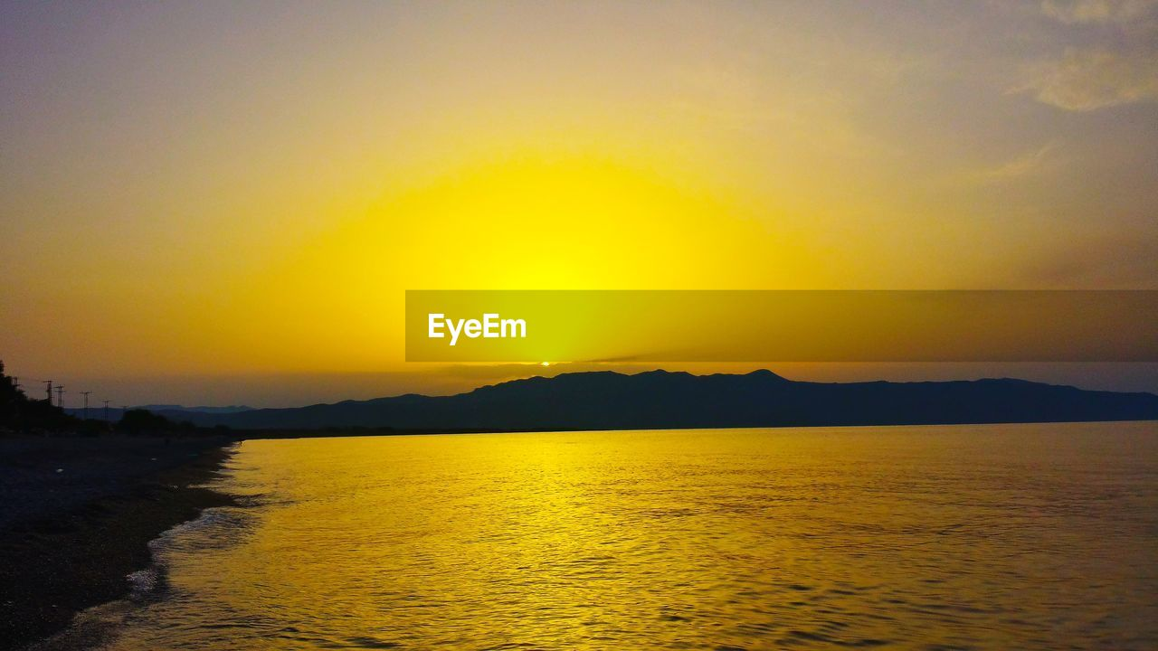 sunset, yellow, silhouette, beauty in nature, scenics, nature, water, tranquility, tranquil scene, sea, sky, no people, outdoors, mountain