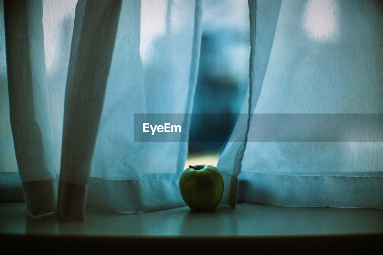 Close-Up Of Granny Smith Apple On Window Sill
