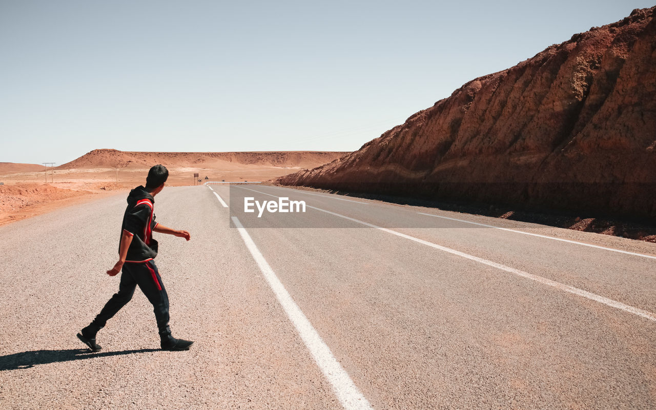 road, clear sky, landscape, one person, desert, full length, real people, arid climate, day, lifestyles, outdoors, nature, sky, mountain, scenics, men, people
