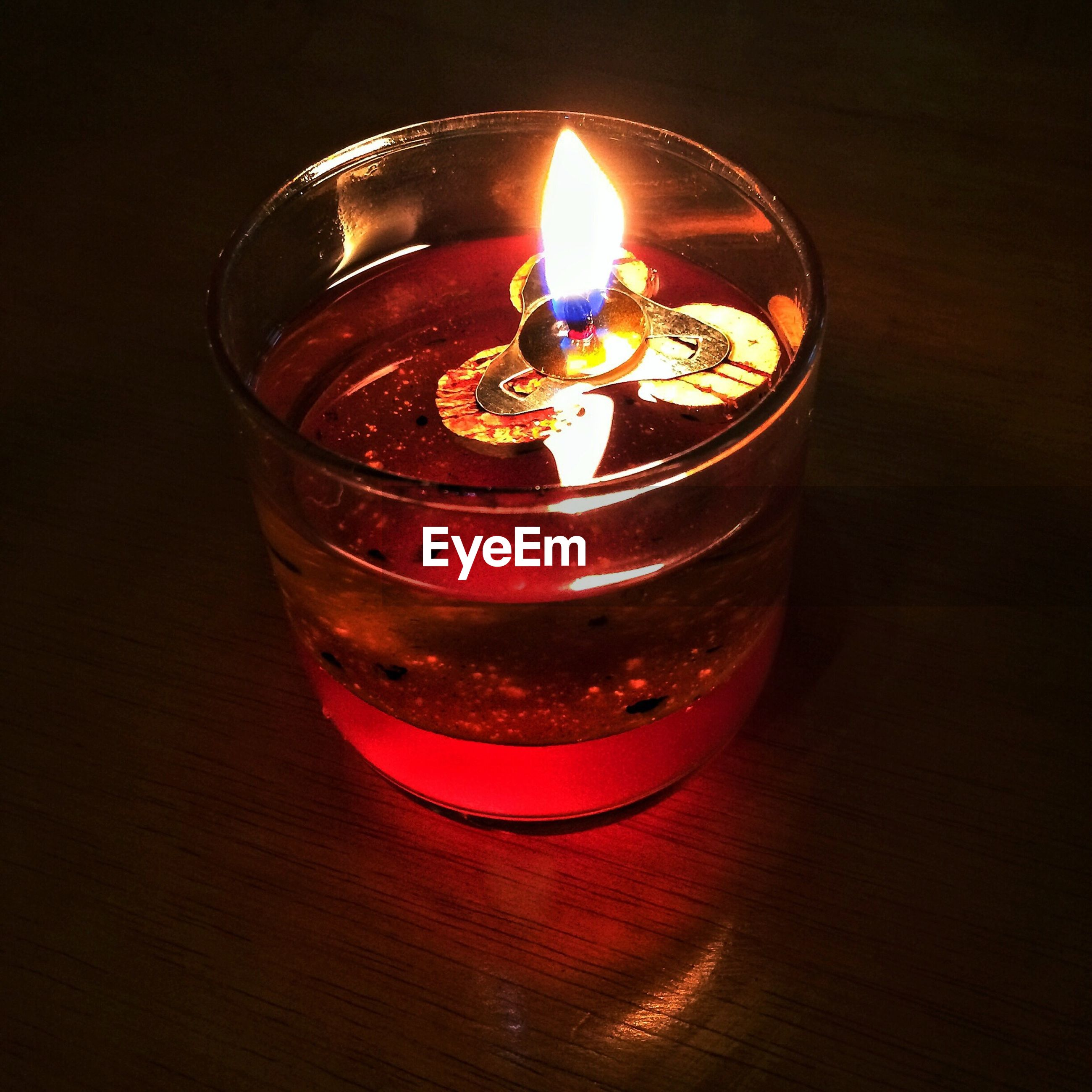 Close-up of lit tea light candle on table in darkroom