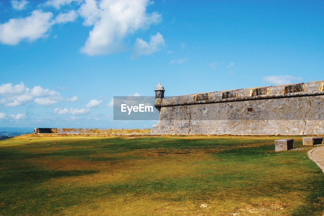architecture, built structure, sky, building exterior, grass, lighthouse, cloud - sky, nature, tower, land, building, day, guidance, no people, security, protection, safety, history, plant, the past, outdoors
