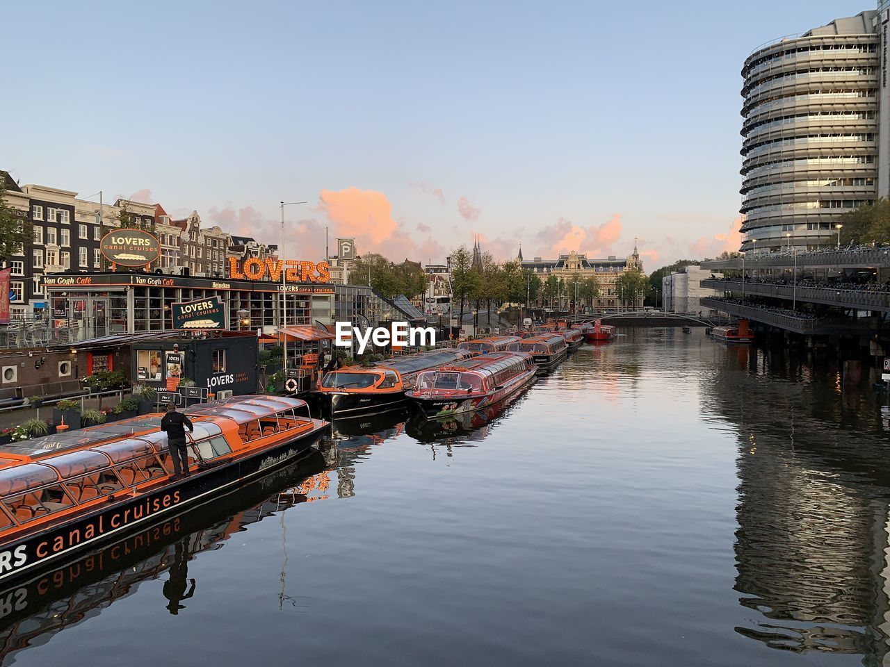 reflection, water, architecture, building exterior, built structure, mode of transportation, sky, transportation, waterfront, nautical vessel, city, nature, building, river, moored, outdoors, day, residential district