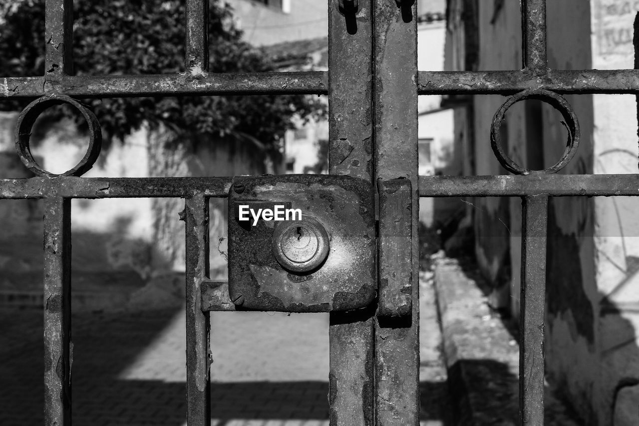metal, focus on foreground, safety, close-up, no people, rusty, security, protection, lock, gate, old, day, closed, padlock, entrance, door, outdoors, abandoned, architecture, run-down, safe, wrought iron, latch