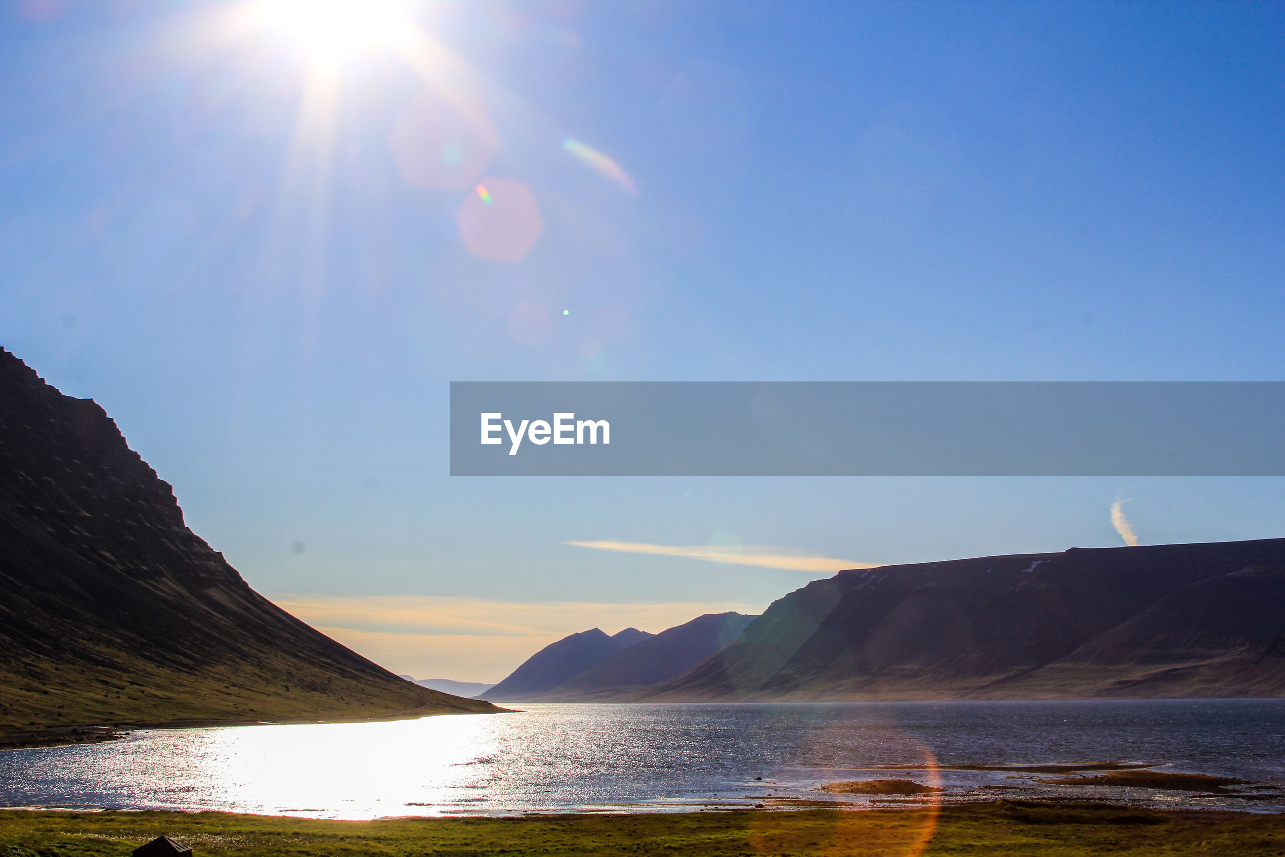 Scenic view of sun shining over lake and mountains