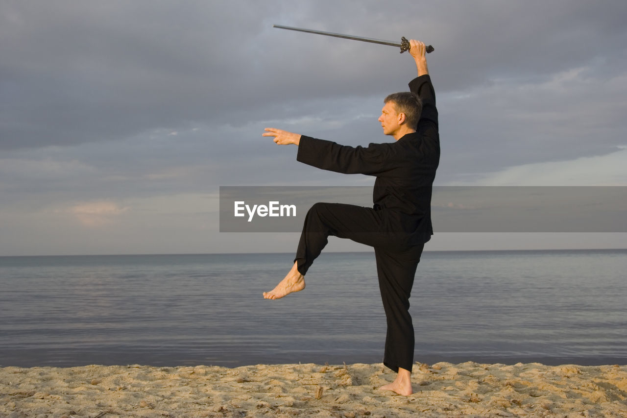 Man Practicing Tai Chi On Sand At Beach