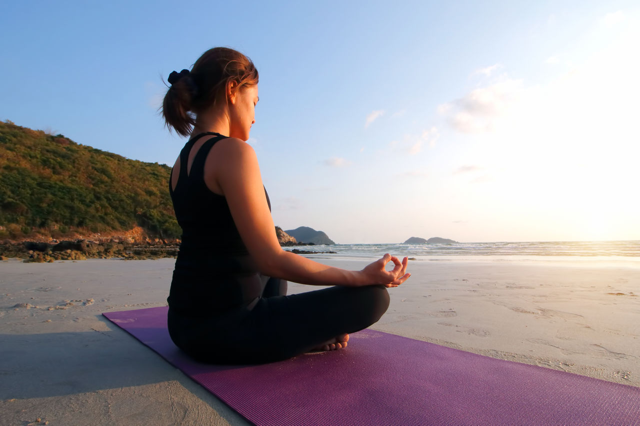 Young woman practicing yoga at beach against sky during sunset
