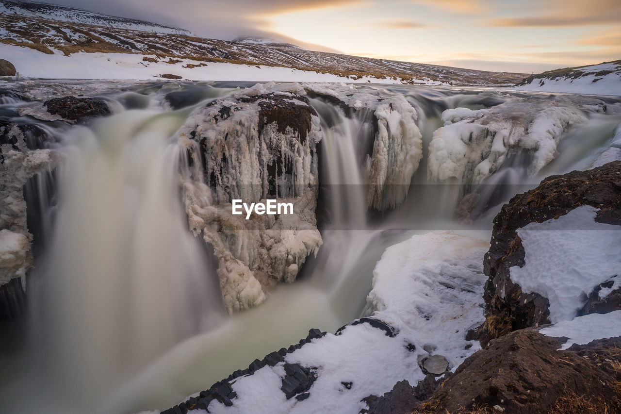 SCENIC VIEW OF WATERFALL IN SNOW