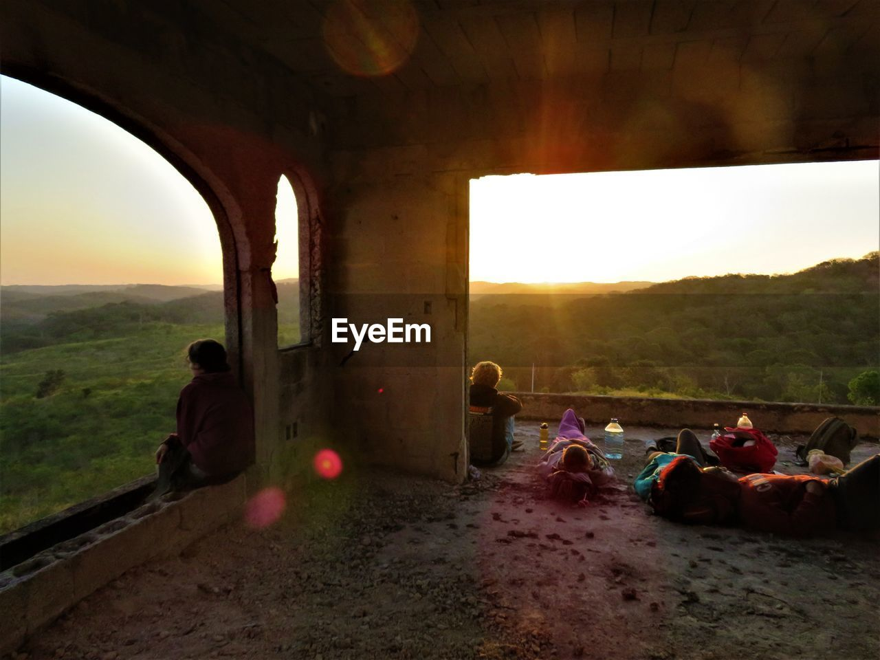 real people, men, sky, window, women, lifestyles, leisure activity, architecture, day, built structure, sunset, nature, landscape, large group of people, togetherness, mountain, outdoors, sitting, adult, people