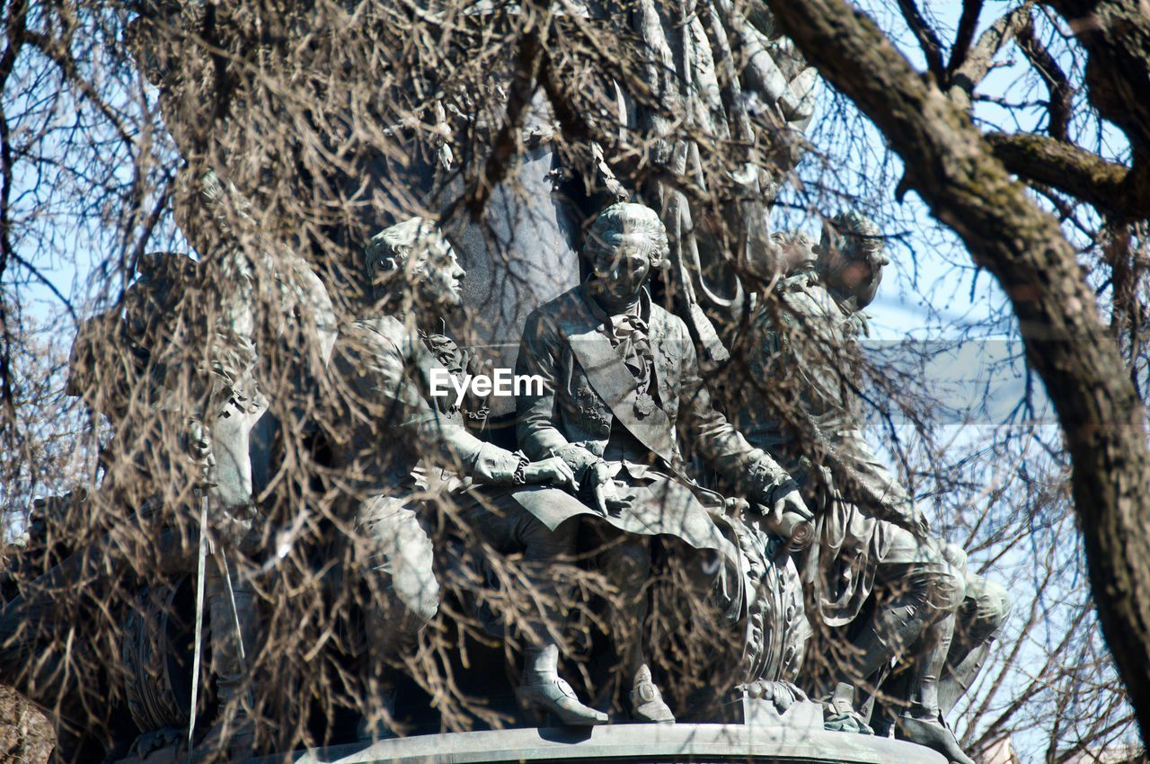 tree, sculpture, low angle view, art and craft, representation, statue, no people, human representation, day, branch, plant, creativity, male likeness, nature, outdoors, craft, bare tree, cold temperature, tree trunk, trunk, government