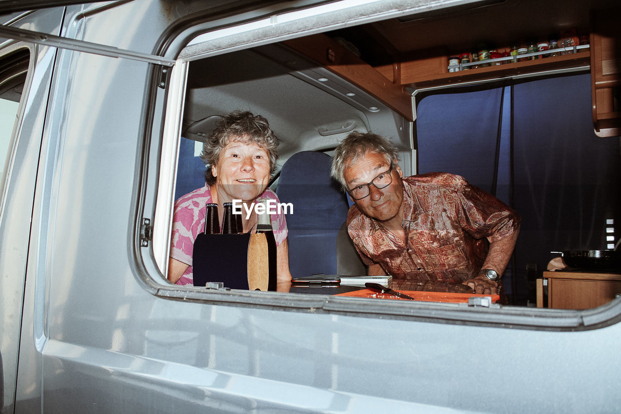 Portrait of senior couple in motor home seen through window