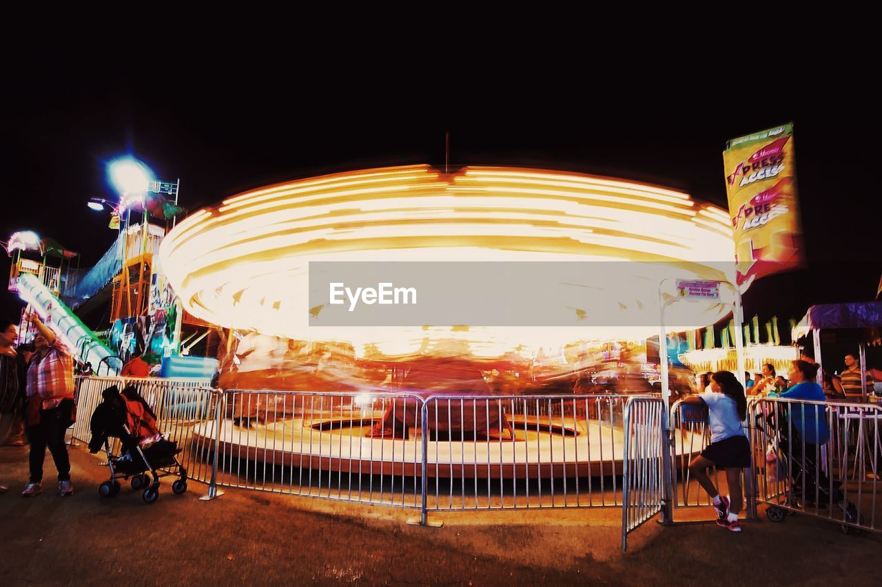 night, illuminated, real people, leisure activity, arts culture and entertainment, amusement park, motion, enjoyment, long exposure, men, outdoors, large group of people, blurred motion, clear sky, rear view, lifestyles, amusement park ride, full length, women, togetherness, carousel, sky, people